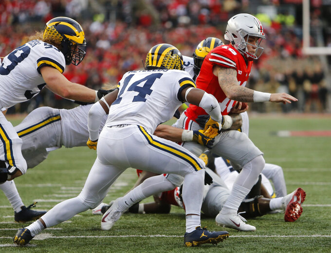 Ohio State quarterback Tate Martell, right, is tackled by Michigan defenders during the second half of an NCAA college football game Saturday, Nov. 24, 2018, in Columbus, Ohio. Ohio State beat Michigan 62-39. (AP Photo/Jay LaPrete)