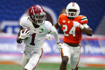 Alabama wide receiver Jameson Williams (1) runs away from Miami safety Kamren Kinchens (24) for a touchdown after a catch in the second half of an NCAA college football game Saturday, Sept. 4, 2021, in Atlanta. (AP Photo/John Bazemore)