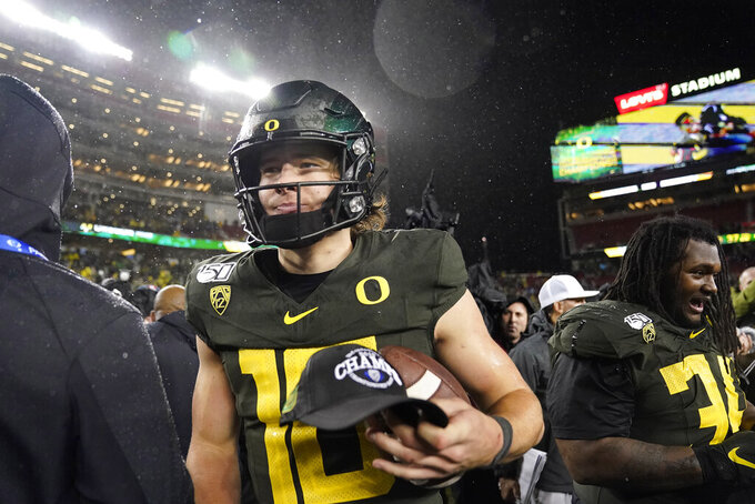 Oregon quarterback Justin Herbert walks off the field after Oregon defeated Utah 37-15 in an NCAA college football game for the Pac-12 Conference championship, in Santa Clara, Calif., Friday, Dec. 6, 2018. (AP Photo/Tony Avelar)