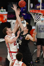 Utah's Riley Battin (21) shoot around Washington's Riley Sorn (52) during the first half of an NCAA college basketball game in the first round of the Pac-12 men's tournament Wednesday, March 10, 2021, in Las Vegas. (AP Photo/John Locher)