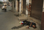 In this Oct. 31, 2019, photo, an Indian drug user lies unconscious by the side of a road in Kapurthala, in the northern Indian state of Punjab. Mass abuse of the opioid tramadol spans continents, from India to Africa to the Middle East, creating international havoc some experts blame on a loophole in narcotics regulation and a miscalculation of the drug's danger. Punjab, the center of India's opioid epidemic, was among the latest to crack down on the tramadol trade. Researchers estimate about 4 million Indians use heroin or other opioids, and a quarter of them live in the Punjab, India's agricultural heartland bordering Pakistan. (AP Photo/Channi Anand)