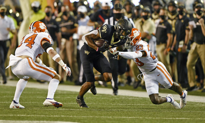 Wake Forest wide receiver Donavan Greene is stopped by Clemson defenders Nolan Turner (24) and Andrew Booth Jr. (23) in the first half of an NCAA college football game Saturday, Sept. 12, 2020, in Winston-Salem, N.C. (Walt Unks/The Winston-Salem Journal via AP)