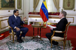 Venezuela's President Nicolas Maduro, left, speaks during an interview with Associated Press Vice President of International News, Ian Phillips, at Miraflores presidential palace in Caracas, Venezuela, Thursday, Feb. 14, 2019. Even while criticizing Donald Trump's confrontational stance toward his socialist government, Maduro said he holds out hope of meeting the U.S. president to resolve an impasse over his recognition of opponent Juan Guaido as Venezuela's rightful leader. (AP Photo/Ariana Cubillos)