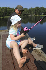 Tessa King, 4, tries catching a fish for first time with her father, Shawn King, on Friday, July 5, 2019, at Jewel Lake in Anchorage, Alaska. She took off her shoes and proclaimed,
