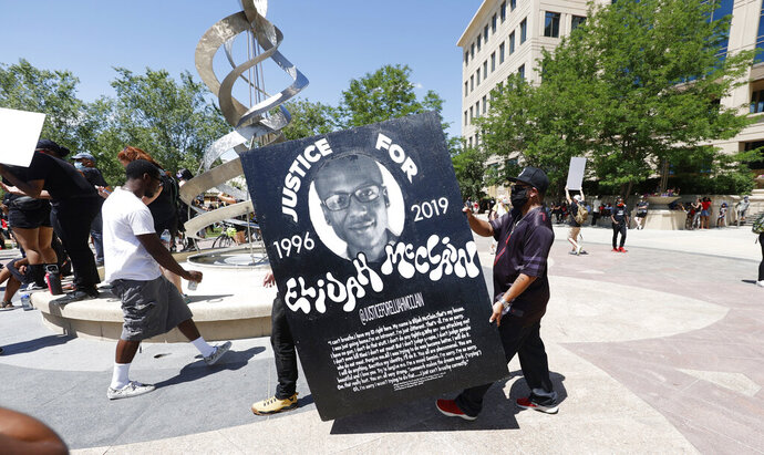 FILE - In this June 27, 2020, file photo, demonstrators carry a giant placard during a rally and march over the death of 23-year-old Elijah McClain outside the police department in Aurora, Colo. Multiple suburban Denver police officers have been placed on paid administrative leave amid an investigation into photos of them related to the case of a Black man who died last summer after he was stopped and restrained, police said Monday, June 29, 2020. The interim police chief of the city of Aurora, Vanessa Wilson, said in a statement that the suspended officers were