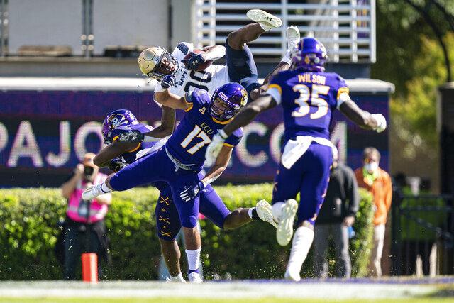 Navy wide receiver Mark Walker (80) tries to hurdle over East Carolina defensive back Warren Saba (17) during an NCAA football game on Saturday, Oct. 17, 2020, in Greenville, N.C. (AP Photo/Jacob Kupferman)