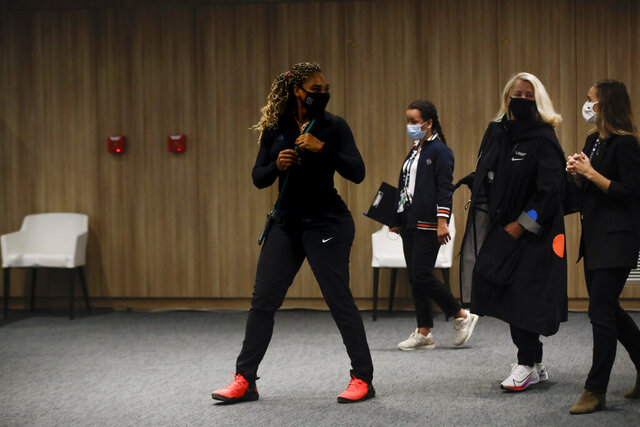 Serena Williams of the U.S., center, leaves after a video link press conference in which she announced her withdrawal from the tournament because of an Achilles injury prior to her second round match of the French Open tennis tournament at the Roland Garros stadium in Paris, France, Wednesday, Sept. 30, 2020. (AP Photo/Alessandra Tarantino)