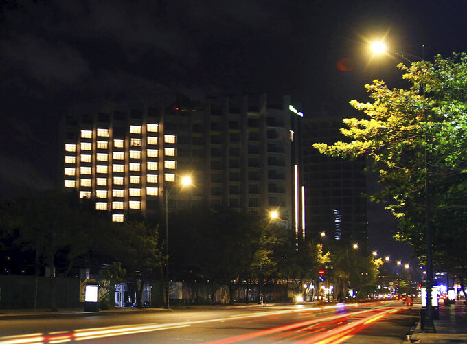 In this Wednesday, April 22, 2020, photo, rooms at ibis style's hotel in Vung Tau, Vietnam, are lit up, forming a heart shape to support the country unity in the fight against COVID-19. The world inched toward a new phase in the coronavirus crisis on Thursday, as some countries like Vietnam and New Zealand with few new cases moved toward ending their shutdowns while others like Singapore and Japan were tightening measures to prevent a surge in infections. (AP Photo/Thanh Tu)