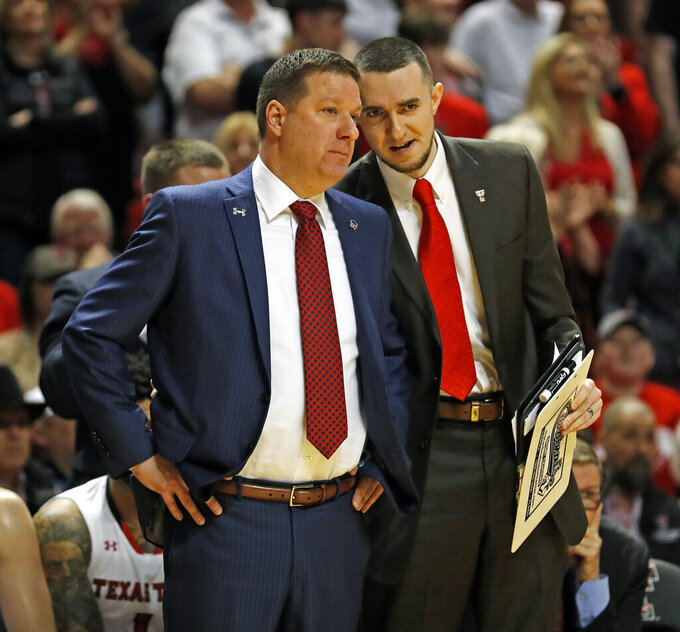 Texas Tech coach Chris Beard, left, talks to assistant coach Max Lefevre during the first half of an NCAA college basketball game against West Virginia, Monday, Feb. 4, 2019, in Lubbock, Texas. (AP Photo/Brad Tollefson)
