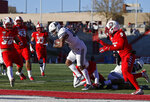 Utah State wide receiver Jordan Nathan (16) crosses the goal line for a touchdown against New Mexico defensive lineman Joey Noble (98) and safety Jerrick Reed (9) during the first half of an NCAA college football game on Saturday, Nov. 30, 2019 in Albuquerque, N.M. (AP Photo/Andres Leighton)