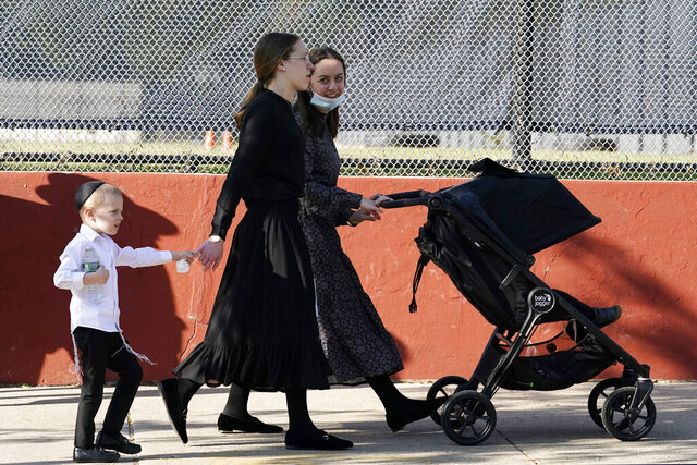 Two young women walk with children during the Jewish holiday of Sukkot, Sunday, Oct. 4, 2020, in the Borough Park neighborhood of New York. New York City's mayor says he has asked the state for permission to close schools and reinstate restrictions on nonessential businesses in several neighborhoods because of a resurgence of the coronavirus. Shutdowns would happen starting Wednesday in nine zip codes in the city, including Borough Park. (AP Photo/Kathy Willens)
