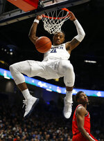 Xavier forward Tyrique Jones (4) dunks in front of St. John's forward Josh Roberts, right, during the first half of an NCAA college basketball game, Sunday, Jan. 5, 2020, in Cincinnati. (AP Photo/Gary Landers)