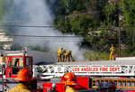 Los Angeles firefighters knock down hot spots on the roof of a music studio in Los Angeles Saturday, April. 14, 2018. Officials says two people were killed and at least three others were hurt when flames ripped through the studio. Fire spokeswoman Amy Bastman says crews found heavy smoke when they responded shortly before 7 a.m. Saturday in the Universal City area north of downtown.  (AP Photo/Damian Dovarganes)