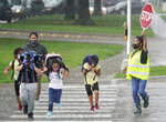 A crossing guard stops traffic for elementary school children to make their way across the street after school let out during a rain storm in Richardson, Texas, Wednesday, Sept. 9, 2020. Many schools across Texas resumed face to face classes this week. (AP Photo/LM Otero)