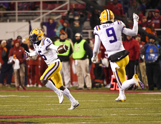 LSU defender Kary Vincent Jr. (5) celebrates after making an interception against Arkansas during the second half of an NCAA college football game, Saturday, Nov. 10, 2018, in Fayetteville, Ark. LSU won, 24-17. (AP Photo/Michael Woods)