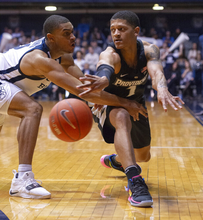Providence guard Makai Ashton-Langford (1) makes a pass to a teammate around the defense of Butler guard Aaron Thompson (2) during the second half of an NCAA college basketball game, Tuesday, Feb. 26, 2019, in Indianapolis. Providence won 73-67. (AP Photo/Doug McSchooler)