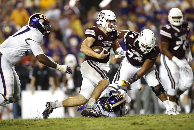 Mississippi State quarterback Nick Fitzgerald (7) runs the ball past LSU defensive end Glen Logan (97) during an NCAA college football game in Baton Rouge, La., Saturday, Oct. 20, 2018. LSU won 19-3. (AP Photo/Tyler Kaufman)