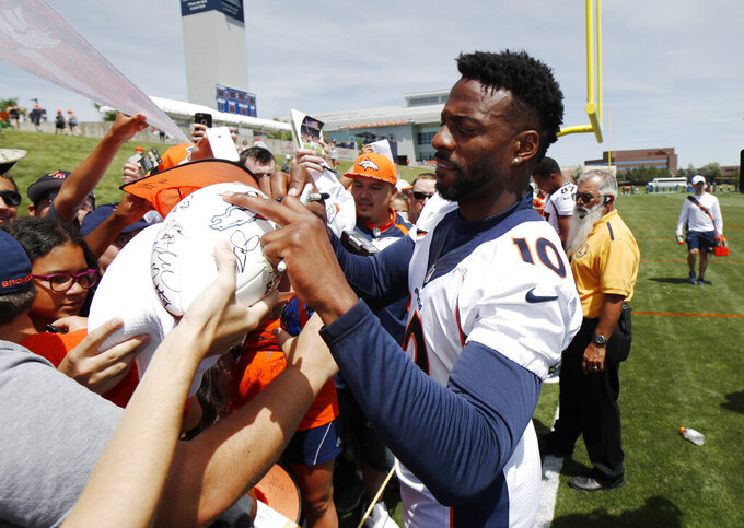 Denver Broncos wide receiver Emmanuel Sanders signs autographs for fans after the opening day of the team's NFL football training camp Thursday, July 18, 2019, in Englewood, Colo. (AP Photo/David Zalubowski)