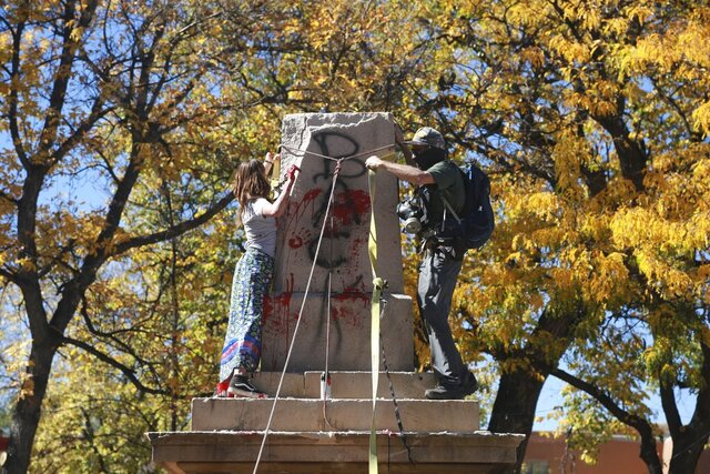 Demonstrators secure a rope around the centerpiece of a solid stone obelisk before tearing it down on Monday, Oct. 12, 2020, in Santa Fe, New Mexico. In July, activists called for the monument to be removed during peaceful protests. On Monday, a group of around 50 protesters pulled down segments of the memorial, which commemorates federal soldiers who fought against Indigenous people in the 19th Century. A reference to