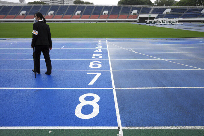 A police officer stands at empty race track after the unveiling ceremony for Olympic Flame of the Tokyo 2020 Olympic torch relay at Komazawa Olympic Park, which was initially built for the 1964 Tokyo Olympic Games, Friday, July 9, 2021, in Tokyo. (AP Photo/Eugene Hoshiko)