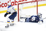 St. Louis Blues' David Perron (57) scores the winning goal in overtime against Winnipeg Jets goaltender Connor Hellebuyck (37) in NH hockey game action in Winnipeg, Manitoba, Friday, Dec. 27, 2019. (John Woods/The Canadian Press via AP)