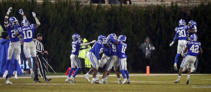 Duke players celebrate after recovering a Miami fumble late in the fourth quarter to seal the win in an NCAA college football game in Durham, N.C., Saturday, Nov. 30, 2019. (AP Photo/Chris Seward)