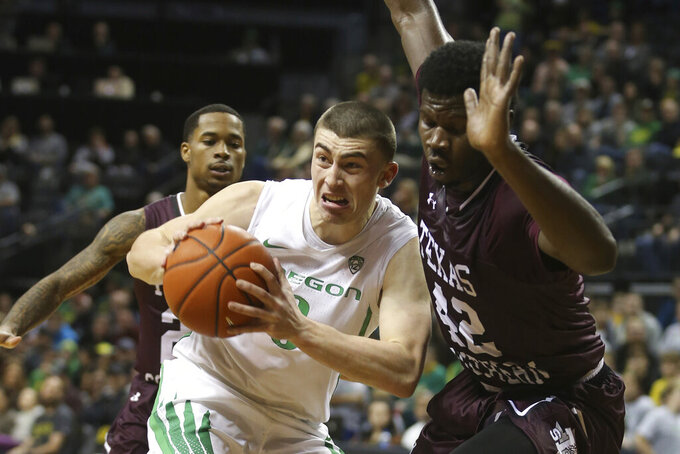 Oregon's Payton Pritchard, center, looks for an open teammate under pressure from Texas Southern's Tyrik Armstrong, left, and Jethro Tshisumpa, right, during the first half of an NCAA college basketball game in Eugene, Ore., Saturday, Dec. 21, 2019. (AP Photo/Chris Pietsch)