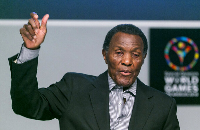 FILE - In this July 20, 2015, file photo, Olympic gold medalist and philanthropist Rafer Johnson lifts his arm to mimic the lighting of the Olympic torch as he recalls the first Special Olympics World Games he attended, during a news conference in Los Angeles. Rafer Johnson, who won the decathlon at the 1960 Rome Olympics and helped subdue Robert F. Kennedy's assassin in 1968, died Wednesday, Dec. 2, 2020. He was 86. He died at his home in the Sherman Oaks section of Los Angeles, according to family friend Michael Roth.(AP Photo/Damian Dovarganes)