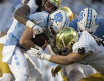 North Carolina quarterback Sam Howell (7) is sacked by Notre Dame's Marist Liufau (35) and Drew White (40) in the second quarter of an NCAA college football game, Friday, Nov. 27, 2020, at Kenan Stadium in Chapel Hill, N.C. (Robert Willett/The News & Observer via AP)