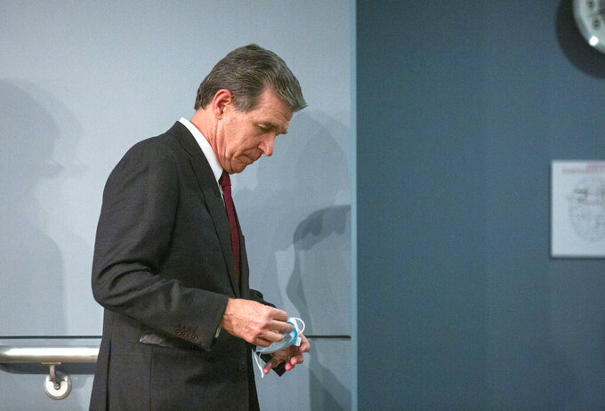 Gov. Roy Cooper heads back after delivering a briefing on North Carolina's coronavirus pandemic response Monday, Jun. 15, 2020, at the N.C. Emergency Operations Center in Raleigh, N.C. (Casey Toth/The News & Observer via AP)