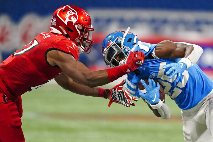 Mississippi running back Henry Parrish Jr. (25) is dragged down by Louisville defensive back Kenderick Duncan (27) during the first half of an NCAA college football game, Monday, Sept. 6, 2021, in Atlanta. (AP Photo/John Bazemore)