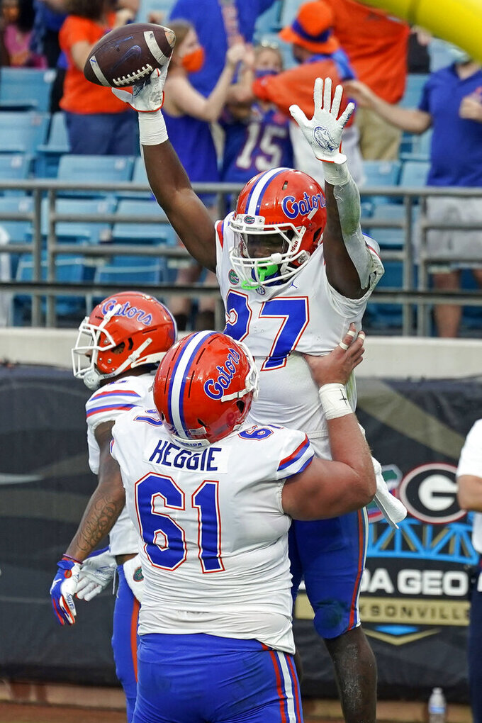 Florida running back Dameon Pierce (27) celebrates his two-yard touchdown run against Georgia with offensive lineman Brett Heggie (61) during the first half of an NCAA college football game, Saturday, Nov. 7, 2020, in Jacksonville, Fla. (AP Photo/John Raoux)