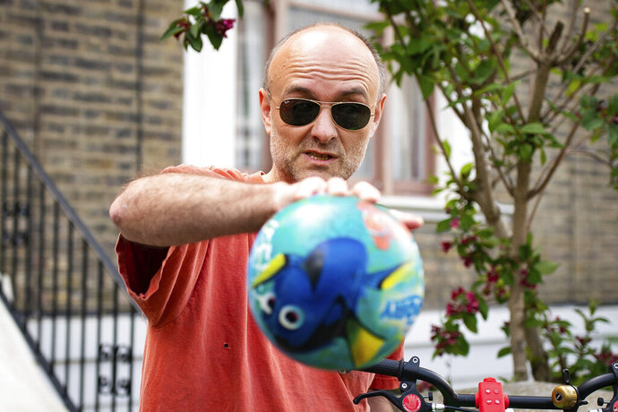 Britain's Prime Minister Boris Johnson's senior aid Dominic Cummings leaves his home, in London, Saturday May 23, 2020. The British government faced accusations of hypocrisy on Saturday after the revelation that Prime Minister Boris Johnson's top adviser Cummings, traveled more than 250 miles (400 kms) to his parents' house during a nationwide lockdown while he was showing coronavirus symptoms. (Aaron Chown/PA via AP)