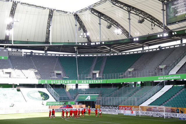 Munich's players celebrate in front of the empty stands after  the German Bundesliga soccer match between VfL Wolfsburg and FC Bayern Munich in Wolfsburg, Germany, Saturday, June 27, 2020. Bayern wins the 8th straight Bundesliga title. (Kai Pfaffenbach/Pool Photo via AP)
