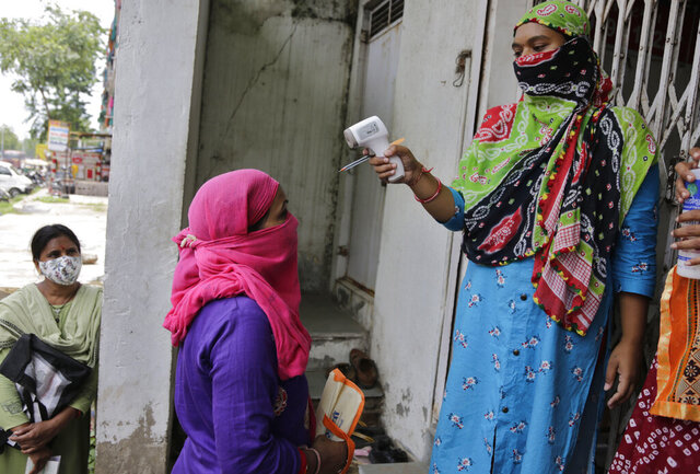 An Indian woman's temperature is checked by another before she enters a bank in Ahmedabad, India, Monday, July 20, 2020. The country of 1.4 billion people, has the third most number of coronavirus cases in the world. (AP Photo/Ajit Solanki)