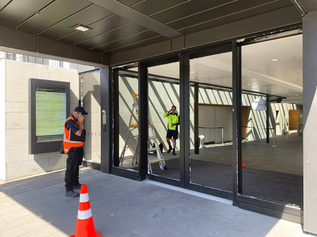 Crews at New Zealand's Parliament inspect the smashed front doors on Wednesday, Jan. 13, 2021, in Wellington, New Zealand. Police said a man armed with an axe smashed the glass doors but did not attempt to enter the building. (AP Photo/Nick Perry)