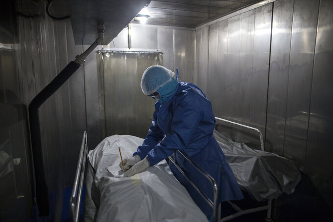 A healthcare worker fills out paper work for a patient who died from COVID-19, in a morgue at the Samaritana Hospital in Bogota, Colombia, Thursday, June 3, 2021. Colombia has become a pandemic hotspot experiencing a third wave of COVID-19 infections and a surge in deaths. (AP Photo/Ivan Valencia)