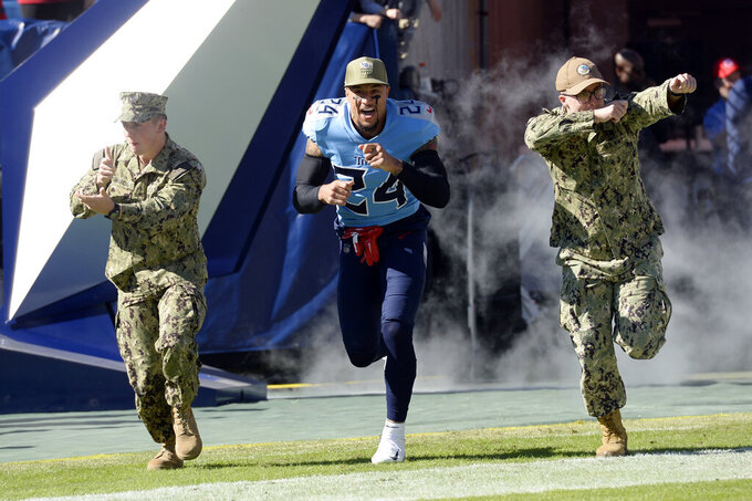 Tennessee Titans strong safety Kenny Vaccaro (24) runs onto the field with members of the military before an NFL football game against the Kansas City Chiefs Sunday, Nov. 10, 2019, in Nashville, Tenn. (AP Photo/Mark Zaleski)
