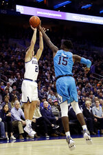 Villanova's Collin Gillespie, left, goes up to shoot against Georgetown's Jessie Govan during the first half of an NCAA college basketball game, Sunday, Feb. 3, 2019, in Philadelphia. (AP Photo/Matt Slocum)