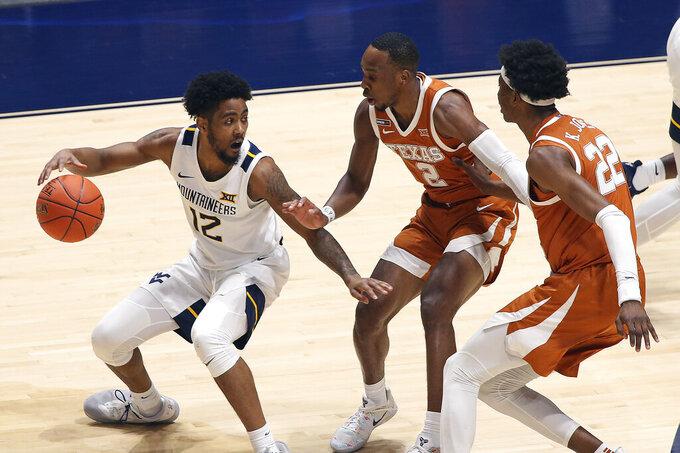 West Virginia guard Taz Sherman (12) is defended by Texas guard Matt Coleman III (2) and forward Kai Jones (22) during the second half of an NCAA college basketball game Saturday, Jan. 9, 2021, in Morgantown, W.Va. (AP Photo/Kathleen Batten)