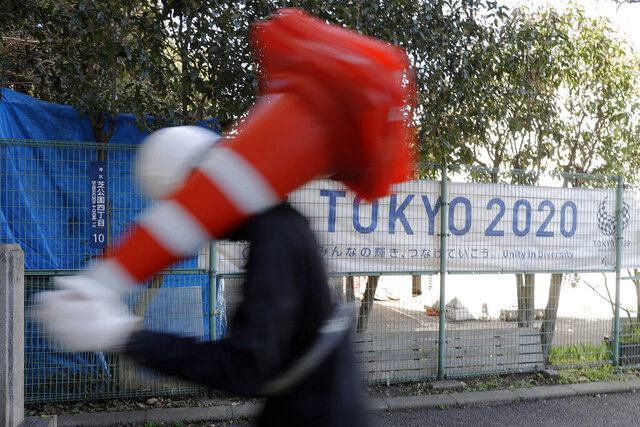 A worker on duty at a road construction site walks past a banner promoting the 2020 Olympic Games in Tokyo, Friday, March 20, 2020. The Olympic flame from Greece arrived in Japan even as the opening of the the Tokyo Games in four months is in doubt with more voices suggesting the games should to be postponed or canceled because of the worldwide virus pandemic. (AP Photo/Gregorio Borgia)