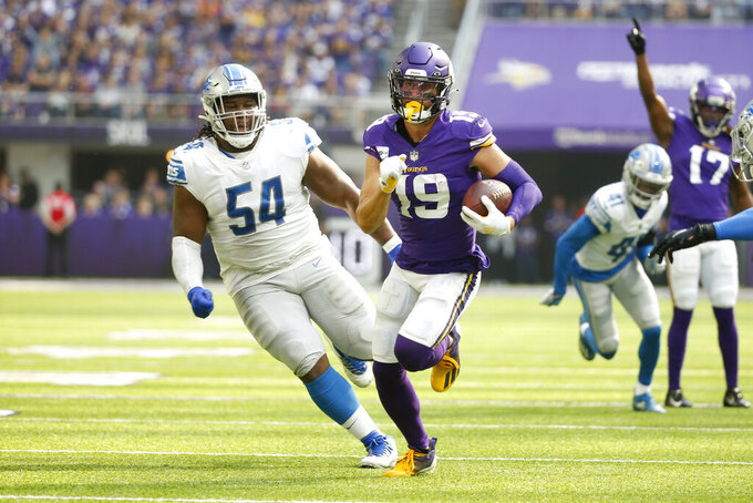 Minnesota Vikings wide receiver Adam Thielen (19) runs from Detroit Lions nose tackle Alim McNeill (54) after catching a pass during the first half of an NFL football game, Sunday, Oct. 10, 2021, in Minneapolis. (AP Photo/Bruce Kluckhohn)