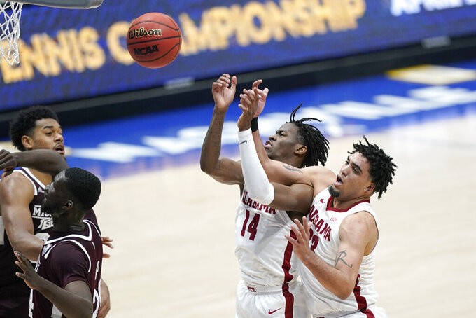 Alabama's Keon Ellis (14) and James Rojas (33) collide while reaching for a rebound in the second half of an NCAA college basketball game against Mississippi State in the Southeastern Conference Tournament Friday, March 12, 2021, in Nashville, Tenn. (AP Photo/Mark Humphrey)