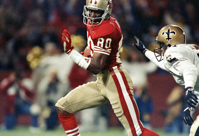 FILE - In this Nov. 7, 1989, file photo, San Francisco 49ers wide receiver Jerry Rice runs past New Orleans Saints' Toi Cook for a touchdown in the first half of an NFL football game at Candlestick Park in San Francisco. Rice set records with 1,549 catches, 22,895 yards receiving and 208 TDs, while helping the Niners win three Super Bowl titles. (AP Photo/Martha Jane Stanton, File)