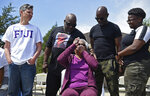 """Jessie Hamilton, seated, reacts as she is presented with a check to pay off her mortgage as LSU FIJI graduates gather to surprise their former house kitchen staff member, Saturday, April 3, 2021, and celebrate """"Jessie Hamilton Day"""" in Baker, La. Behind her are, from left, FIJI graduate Andrew Fusaiotti, Hamilton's sons Andre' Hamilton and Craig Hamilton, and her granddaughter, Jamiah Hamilton. (Hilary Scheinuk/The Advocate via AP)"""