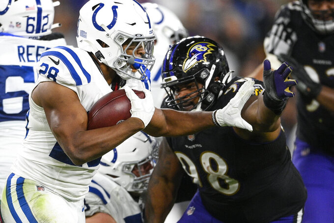 Indianapolis Colts running back Jonathan Taylor (28) stiff-arms Baltimore Ravens nose tackle Brandon Williams (98) during the second half of an NFL football game Monday, Oct. 11, 2021, in Baltimore. (AP Photo/Nick Wass)
