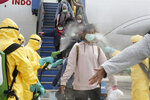 FILE - In this Feb. 2, 2020, file photo released by the Indonesian Foreign Ministry, Indonesians who arrived from Wuhan, China, are sprayed with antiseptic at Hang Nadim Airport in Batam, Indonesia. The virus outbreak that began in China and has spread to more than 20 countries is stretching already-strained public health systems in Asia and beyond, raising questions over whether everyone can get equal access to treatment. (Indonesian Foreign Ministry via AP, File)