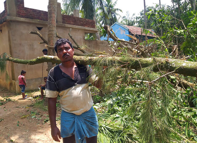 A villager clears tree branches fallen in front of his house after Cyclone Amphan hit the region, at Baguranjalpai village in East Midnapore district in West Bengal state, India, Friday, May 22, 2020. People forgot about social distancing and crammed themselves into government shelters, minutes before Cyclone Amphan crashed in West Bengal. The cyclone killed dozens of people and the coronavirus nine in this region, one of India's poorer states. Even before the cyclone, its pandemic response was lagging; the state has one of the highest fatality rates from COVID-19 in India. With an economy crippled by India's eight-week lockdown, and health care systems sapped by the virus, authorities must tackle both COVID-19 and the cyclone's aftermath.(Debasis Shyamal via AP)