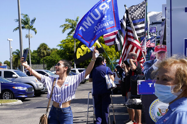 Juliet Roa takes a selfie as supporters of President Donald Trump wave flags outside of an early voting location at the John F. Kennedy Library, Tuesday, Oct. 27, 2020, in Hialeah, Fla. (AP Photo/Lynne Sladky)