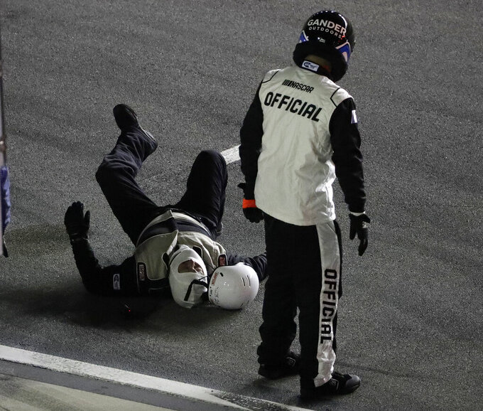 A crew member for the Bryan Dauzat truck lies on his back after he was hit by the truck on pit road during the NASCAR Truck Series auto race Friday, Feb. 15, 2019, at Daytona International Speedway in Daytona Beach, Fla. The crew member was taken away in an ambulance. (AP Photo/Chris O'Meara)